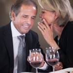 Cheerful Woman Whispering Something In Man's Ear In A Elegant Restaurant
